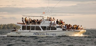 A boat loaded with tourists from Princess Island on a sunset cruise.